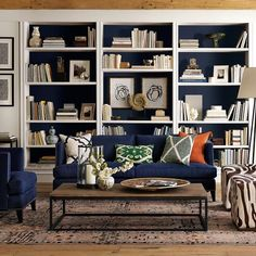 Bookcase with navy background || navy, green, and orange pillows
