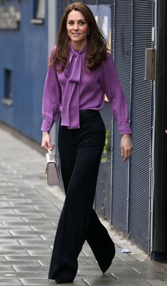 Kate Middleton pairs a purple Gucci blouse with black trousers and matching pumps at a visit to London's Henry Fawcett Children's Centre. Vestido Kate Middleton, Kate Middleton Bikini, Kate Middleton New Hair, Looks Kate Middleton, Kate Middleton Wedding, Kate Middleton Outfits, Princess Kate Middleton, Kate Middleton Fashion, Middleton Family
