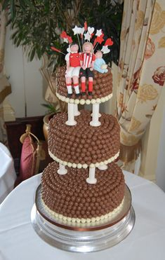 Malteser cake                                                          A 3 tiered cake, stood on pillars, covered in white and milk chocolate Maltesers. On top there is characterchures of the bride and groom.