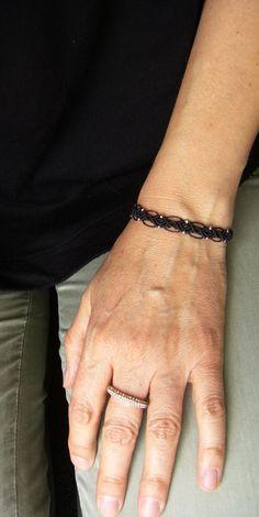 Ein geknüpftes **Armband** in Schwarz mit eingearbeiteten…