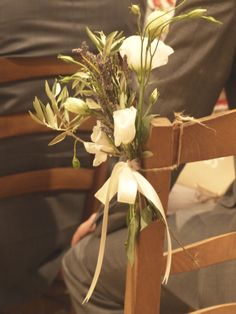 Wedding flowers for the benches in church. white rose with lavender and oliver tree tied with a rustic string and a white bow