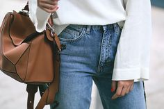 Nisi is wearing: Embroidered boyfriend jeans, shirt with big sleeves, Loewe Puzzle bag, Jimmy Choo Tide sling-back pumps