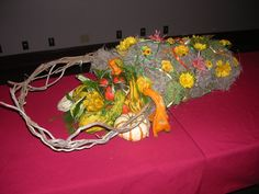 A very large handmade chickenwire basket stuffed with  various types of moss.  I filled the basket with gourds.  On the outside I stuffed fresh flowers which had been placed into water picks into the sides of the chicken wire.  This stayed fresh for a long time.  It could be placed on a table, door, etc.