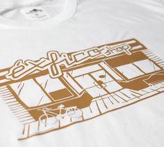 L3. Shop, blanco. Ilustración de fachada de tienda tradicional americana, que simula una éxfico shop con rótulo exterior de gran tamaño, puerta de entrada central de dos hojas, ventanales laterales, acompañada de bicicleta clásica y banco.    Diseño de 26 cm de ancho en color camel. $15.00