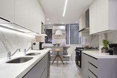 Cozinha com padrão marmorizado nos revestimentos em porcelanato, quartzo branco nas bancadas, e marcenaria cinza. Women's Fashion, Kitchen, Table, Furniture, Home Decor, White Porcelain Tile, White Quartz, White Vanity Desk, Modern White Kitchens