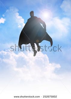 Silhouette of a superhero figure flying on clouds  - stock photo