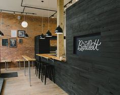the bartlett cafe interior with black washed wood with exposed brick and industrial fixtures