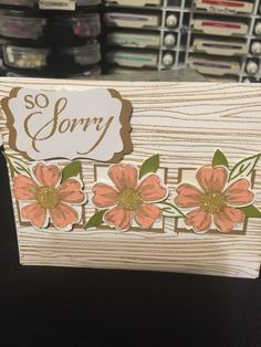 Sorry card with woodgrain embossing in baked brown sugar and pansies in crisp cantaloupe
