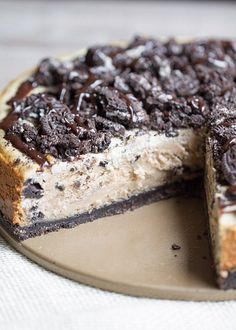 The BEST Peanut Butter Oreo Cheesecake. This creamy peanut butter cheesecake is filled and topped with Oreo cookies and drizzled with hot fudge!   This Gal Cooks