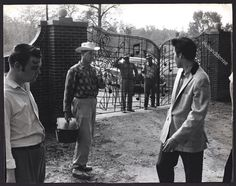 A Vintage 1957 Original Photograph depicting music's new sensation Elvis Presley at the gates of his new castle that will be famously known as Graceland ! The Memphis, Tennessee home would become one of the most-visited private homes in America with over 600,000 visitors a year (second only behind the White House).  This early photo was captured on April 19, 1957 by Commercial Appeal photographer Bob Williams and syndicated by The Galloon Photo Agency of New York when the young monarch of…