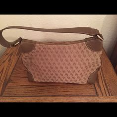 """Dooney & Bourke Authentic Brown Fabric bag Dooney & Bourke Signature Brown Fabric Leather Shoulder Bag. Authentic .  Measurements: 7"""" Tall 13"""" Wide 2&1/2"""" Deep 18"""" Strap length  Gently used, excellent condition.                        No trades, no holding , no off sight payment Dooney & Bourke Bags Shoulder Bags"""