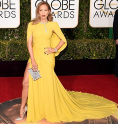 Hello sunshine: Jennifer Lopez wore a form-fitting yellow gown with a saucy slit up one side, paired with dazzling shoes and jewellery