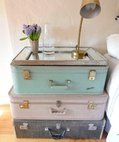 vintage luggage piled up and topped with a mirror for a very glam bedside table.