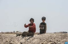 """TURKEY, Akcakale : Syrian refugees ask for water in Akcakale at the  Turkish border near the Syrian town of Tal Abyad, on June 13, 2015.  Turkey said it was taking measures to limit the flow of Syrian refugees  onto its territory after an influx of thousands more over the last days  due to fighting between Kurds and jihadists. Under an """"open-door""""  policy, Turkey has taken in 1.8 million Syrian refugees since the  conflict in Syria erupted in 2011. AFP PHOTO / BULENT KILIC    ..."""