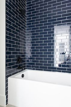 Glossy navy blue backsplash tiles hold a matte black shower kit over a white drop-in bathtub. Navy Bathroom, Bathroom Renos, Modern Bathroom, Small Bathroom, Bathroom Tubs, White Bathrooms, Minimalist Bathroom, Bathroom Cabinets, Bathroom Renovations