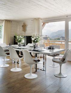 Comedor.La mesa del comedor, realizada en aluminio lacado en blanco y estructura cromada, es una pieza vintage. Las cortinas de mohair blancas son de Adelta.