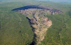 """Uma das maiores crateras da Sibéria, conhecida como a """"porta para o submundo"""", está crescendo tão rapidamente que está descobrindo antigas florestas e carcaças de mais de 200 mil anos"""