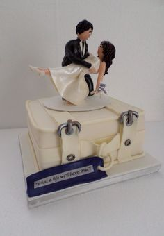Suitcase wedding cake with bride and groom sculptured from modelling chocolate. Created by Villa Chateau