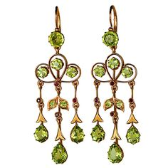 Art Nouveau Russian Peridot Chandelier Earrings.   1900s.   The earrings are handcrafted in rose and green 14K gold and set with round and drop shaped sparkling golden green Uralian chrysolites / peridots.