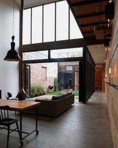 Sala de estar com piso de cimento queimado e jardim aberto