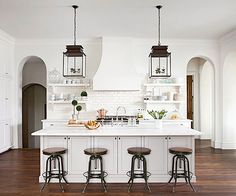 Pair of wrought-iron lantern pendants punctuates the large island topped with honed Calacatta Gold marble. Floating shelves flanking the range hood lighten the look of the kitchen and create beautiful display space.