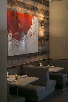 Bold red abstract wall art on reclaimed rustic wooden walls with modern tables and leather booth seating inside Columbia, S.C. Italian restaurant Pasta Fresca. Full-scale commercial interior design by MACK Home.