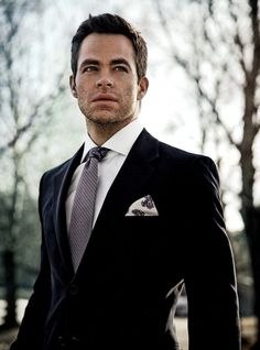 Chris Pine in a solid black suit with a white shirt, purple tie and patterned pocket square
