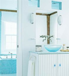 Spa Style- In this spa-like bathroom, blue tile and a modern blue glass sink allow for a serene start to the day. Pairing blue with crisp white in a bath gives the space a clean finish. The color combination can lean cottage, as with the addition of the vintage-inspired beaded-board vanity; with sleek surfaces and fixtures, it can take on a contemporary vibe.