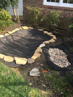 Step 4#  I took weed barrier fabric and placed over the drainage rock to prevent mud from falling into the play area.  I took decorative sand stone rock and outlined the borders of the two pits.