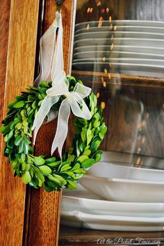 mini boxwood wreath hanging on cabinet atthepicketfence.com