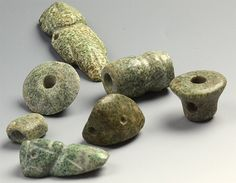 Great collection of Pre-Columbian green hard-stone beads.  Included in the mix are two people and a carved face bead.  Out of the estate of renowned bead collector Naomi Lindstrom.