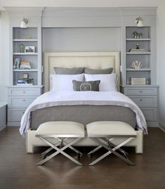 These floor to ceiling book shelves double as a storage and an eye- capturing focal point that surrounds the head board, making the bed in this master bedroom,