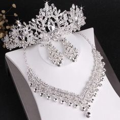 With our Luxury Crystal Beads Bridal Tiara Set, you will truly become a queen for a day. Each piece's multi-faceted crystals provide a light-catching sparkle that will make you stand out from the crowd. From the exquisite earrings that bring a hint of luxury with every turn of your head to the glittering necklace that exudes glamour and the tiara that gives you a regal look, this jewelry set will make you stand out on every occasion. Red & Gold Tiara Set includes: Necklace Earrings Tiara Wedding Party Hair, Wedding Crowns, Wedding Bride, Rhinestone Wedding, Bridal Tiara, Bridal Crown, Wedding Jewelry Sets, Hair Jewelry, Jewellery Box