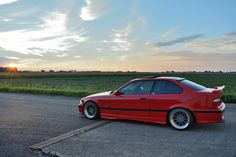 Red BMW e36 coupé on cult classic OZ Hartge Design C wheels
