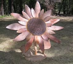 The shortest of our new metal Sunflower sculptures is almost five feet tall. The leaves and petals are all hand cut and shaped. The tractor sprocket base makes it very stable.