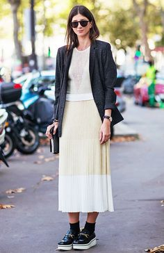 A pleated skirt is worn with a neutral top, blazer, and Céline loafers