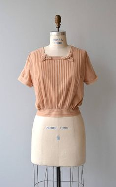 Vintage 1950s pale terra cotta nylon chiffon blouse with front pleating, rosettes at each shoulder, short sleeves, banded waist and back buttons.  --- M E A S U R E M E N T S ---  fits like: medium shoulder: 18 bust: 36-44 waist: up to 30 length: 18 brand/maker: Penny Potter condition: excellent  ➸ More tops & sweaters https://www.etsy.com/shop/DearGoldenVintage?section_id=5800171  ➸ Visit the shop http://www.DearGolden.etsy.com ____________________...