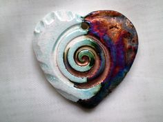 Spiral Heart Focal Bead in Clay with White Crackle and Copper Raku Glaze. $3.00, via Etsy.