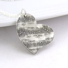 A beautiful, handmade Sterling Silver wild heart textured with my Sheet Music pattern is suspended from a dainty Sterling Silver 1.5mm flat cable