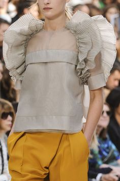 Sheer grey, structured blouse with fine 3D pleat ruffles around the sleeves; fashion details // Chloé