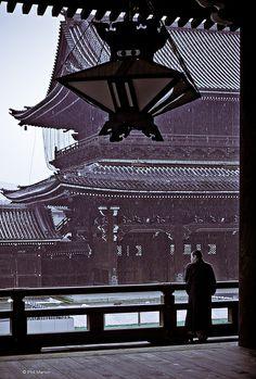 Pensive monk shelters from the rain - Nishi Honganji temple, Kyoto beautiful Japan travel Asian