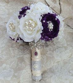 Purple & Ivory Jewel Embellished Brooch Bouquet Simple Elegant custom designed flower bouquet in purple & ivory mix (can be made in purple & white also). Pearl brooches added to each flower center Crystal Bouquet, Ribbon Bouquet, Wedding Brooch Bouquets, Bride Bouquets, Floral Bouquets, Prom Flowers, Silk Flowers, Fabric Flowers, Wedding Flowers