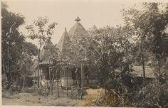 Nigeria, view of Ibo Mbari house. Thatched-roof has several points. Sculptures and wall-paintings visible inside building. Exterior pillars are painted. Surrounded by trees. Medium: Gelatin silver print.