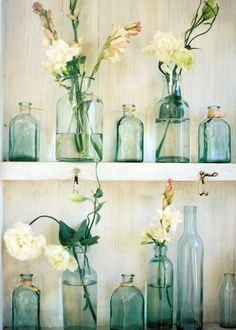 a collection of vintage bottles in the same hue grouped together with spare flower arrangements. Romantic and simple!