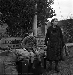 A tired mother and son wait at a crossroads for transport, Luxembourg, 1945    After the liberation of Paris in August 1944, Miller followed the allied forces through Europe. Her eye was very much on the civilians caught up in the war through no fault of their own. This image captures some of the terrible weariness after so many years of conflict.