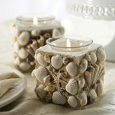seashell votive candle holders Maybe a DIY project - glue on the outside of the glass, cover with sand, spray with clear paint to seal the sand, glue on shells.  add voltive