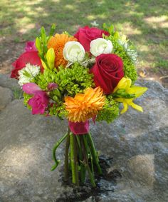 Bridal bouquet of pink dahlias, roses, yellow and pink freesia, orange and white ranunculus, and mini green hydrangea tied with a raspberry pink silk dupioni ribbon.