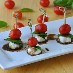 Mini Caprese Bites...beautiful/crowd-pleasing 'as is' or (for a shower) you could cut the tomatoes at a diagonal and form cute little hearts on the skewer.