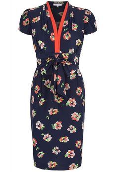 Beautiful silk 1940's inspired tea dress. A Suzannah signature style. Beautifully tailored in silk crepe de chine, printed in an exclusive print designed for the Suzannah brand. A fresh navy coloured ground with tropical colours, off white and pearl grey within the floral. A highlight detail of zingy coral/orange is inserted around the neckline adding a touch of spring- summer to a versatile dress which can be worn from day through to event. Fully lined skirt part . A flattering versatile…