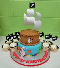 Jake & the Neverland Pirates Cake and cupcakes.  All accents are fondant except for the masts, sails, and the characters behind the portholes.